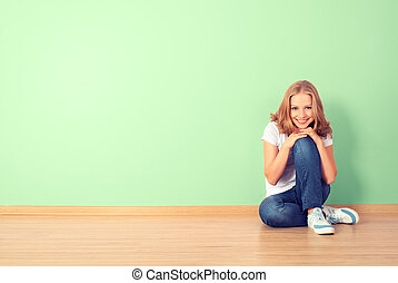 happy  woman is sitting in a room with a blank wall