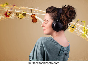 Young woman with headphones listening to music - Pretty...