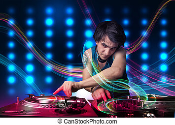 Young Dj mixing records with colorful lights - Attractive...