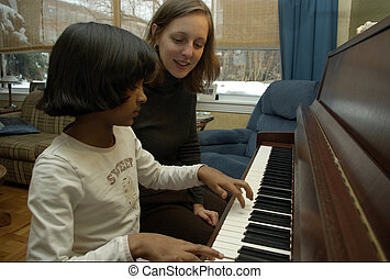piano lesson - young pakistani or indian girl getting...