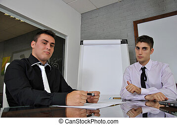 two businessmen sitting in his office with his computer...