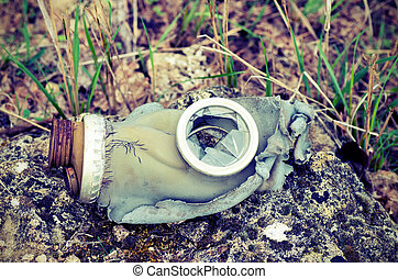 Vintage, broken gas mask lying on a rock on a background of...