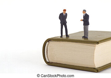 Adult education - Figurine standing on a Book isolated on...