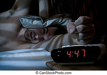 Unhappy man smashing the alarm clock. - Unhappy sleeping man...