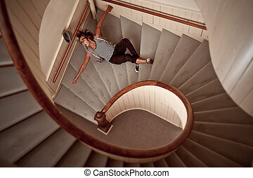 Young man falling down the steep stairs