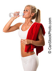 A young girl drinking water after training with a towel on...