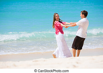 Honeymooners - Romantic couple having fun on white sand...