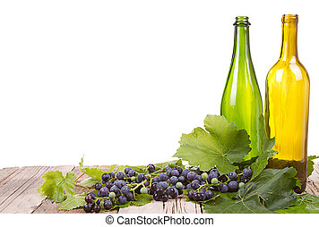 grapes and bottles on wooden plank - grapes on vine with...