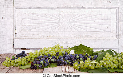 grapes on wooden plank - grapes on vine with leaves sitting...