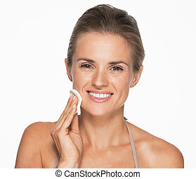 Happy woman using cotton pad to remove makeup