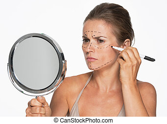 Woman with mirror making plastic surgery marks on face