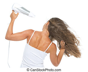 Young woman blow-dry . rear view