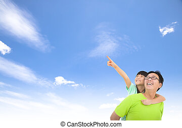 Happy family looking and pointing with cloud background