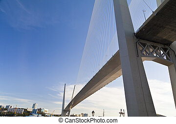 Big suspension bridge in beams of the coming sun against the...