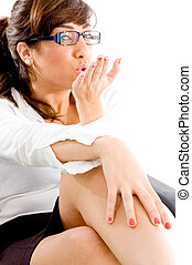 side pose of woman giving flying kiss with white background