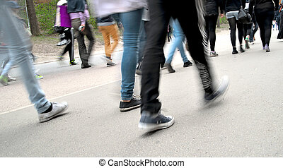 crowd of people walking on road - legs and feet of crowd of...