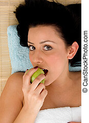 high angle view of smiling woman eating apple in spa - high...