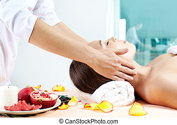 Vital energy - Young woman enjoying relaxing facial massage...