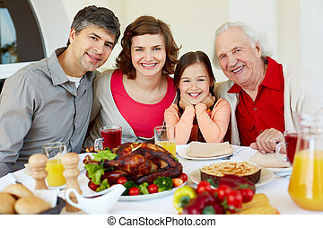Thanksgiving dinner - Portrait of happy family sitting at...