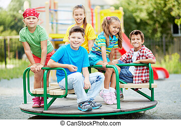 Happy friends - Image of cute friends having fun on carousel...