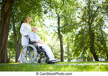Walking in park - Pretty nurse walking with senior patient...