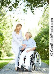 Walking with patient - Pretty nurse walking with senior...
