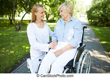 How are you? - Pretty nurse talking to senior patient in a...