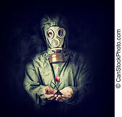 Man in gas mask holding flower in palms - Concept. Hope...