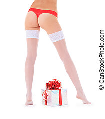 Wonderful female legs in white stockings with christmas gift