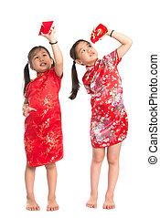 Asian girls peeking into red packet - Happy Asian girls...