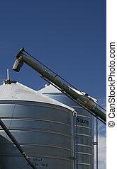 Grain Silos - Agricultural grain silos with blue sky and...