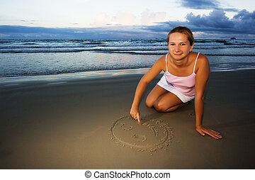 Young woman draws smile near the ocean on sunset time
