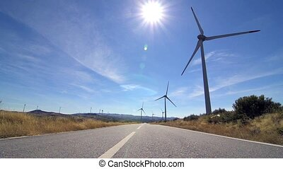 Rotating windmills and paved road. Alternative renewable...