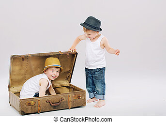 Small boy hiding his elder brother in suitcase - Small kid...