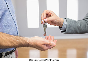 Estate agent giving house key to customer in empty room