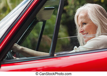 Cheerful mature woman driving red convertible on sunny day