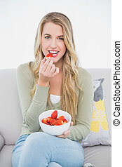 Cheerful pretty blonde eating strawberries sitting on cosy...