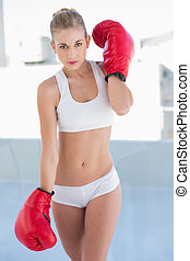Severe young blonde model wearing boxing gloves - Severe...