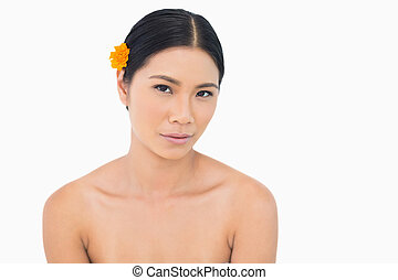 Sensual dark haired model with flower in hair on white...