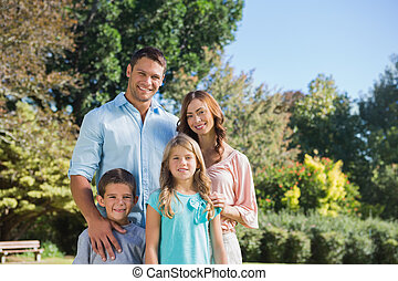 Cheerful family standing in the countryside smiling at...