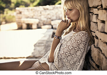 Thoughtful blonde lady leaning on the stone wall -...