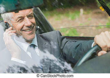 Smiling businessman on the phone driving expensive car