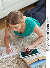 Focused young woman lying on floor using tablet to do her...