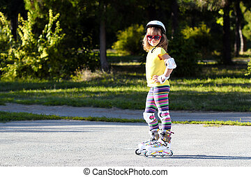 little girl with roller skates and protective skates
