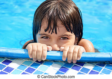 little girl with beautiful eyes peeking out of the pool -...