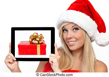 blonde girl in a red Christmas hat on New Year, holding tablet computer touch pad gadget with the gift box on a screen