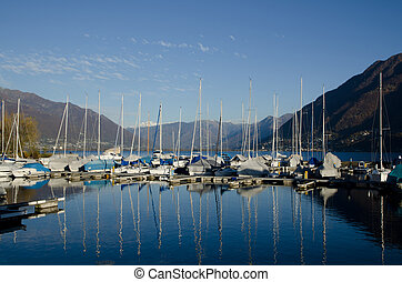 Port on an alpine lake - Boats in the harbour with mountains