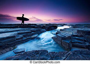 Dawn surfer - A surfer heads out at dawn