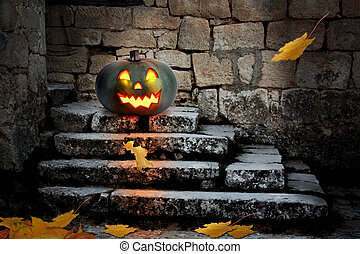 Halloween pumpkins in the yard of an old house at night in...