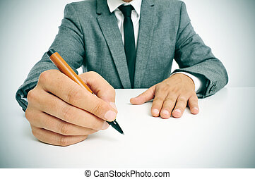 man in suit with a pen in his hand ready to write - man...